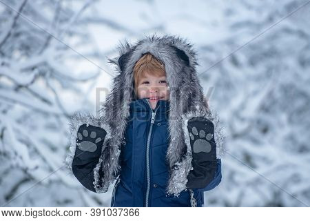Joyful Child Having Fun In Winter Park. Cute Child In Winter Park Trees Covered With Snow. Well Dres