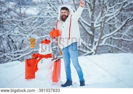 Christmas Shopping With Shopping Bag. Man With Red Gift Playing With Snowman In Winter Park. Christm