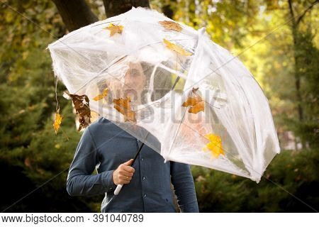 Halloween. Young Man Under An Umbrella With Cobwebs And Spiders On A Halloween Picnic.
