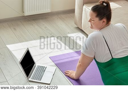 An Overweight Woman Does Yoga At Home Online And Looks At Her Laptop.