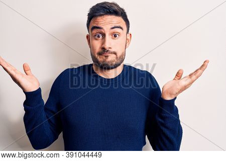 Young handsome man with beard wearing casual sweater standing over white background clueless and confused with open arms, no idea and doubtful face.