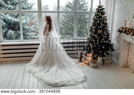 Luxury Bride In Wedding Dress For Christmas Near The Large Panoramic Window. Luxury Bride In Wedding