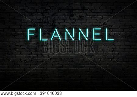 Neon Sign With Inscription Flannel Against Brick Wall. Night View