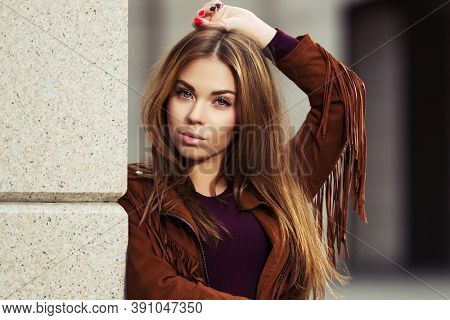 Happy young fashion woman leaning on the wall Stylish female model in brown leather fringe suede jacket with long straight hairs