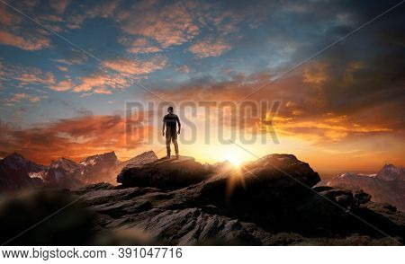 A Man Standing At The Top Of A Mountain As The Sun Begins To Set. Goals, Hopes And Aspirations Conce