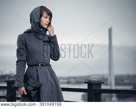 Young fashion woman with handbag walking on city street Stylish female model in gray classic coat and head scarf