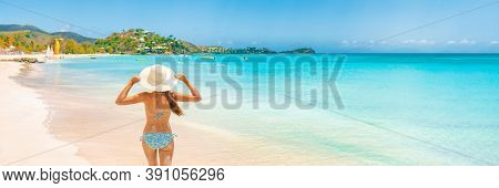 Beach Travel Vacation Holidays Woman walking on Caribbean beach panorama banner background. Rear view of girl tourist in sun hat and bikini on summer holiday vacation destination landscape.