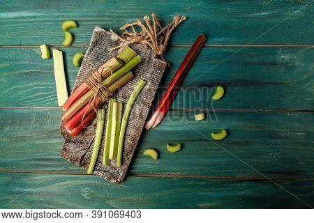 Rhubarb Stalks On A Board, Rhubarb In Bowl On A Wooden Background. Rhubarb Stalks On A Board, Rhubar