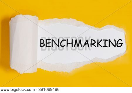 Text Benchmarking Appearing Behind Torn Yellow Paper
