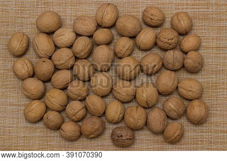 Heap Of Scattered Walnuts In Shell. Walnut Market. Background From Walnuts. Healthy Walnuts. Natural
