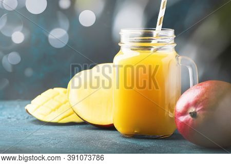 Freshly Squeezed Fresh Mango Juice In Large Glass Jar With Fresh Fruit On Dark Blue Tropical Backgro