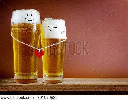 Two Glasses Of Beer With Painted Happy Couple And Red Heart On A String. Valentine Day, Happy Couple