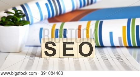 Three Wooden Cubes With Letters Seo, On White Table With Charts,seo Concept