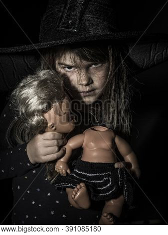 Creepy Young Girl Holding The Separated Head And Body Of An Old Doll For Halloween Theme.
