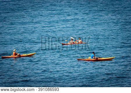 Tellaro, Italy - July 23, 2020: Four People Aboard Their Kayaks, Paddling In The Blue Mediterranean