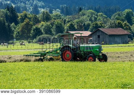 Schwangau, Germany - Sept 9, 2018: Farmer On Tractor With Agricultural Machine For Haymaking, He Arr