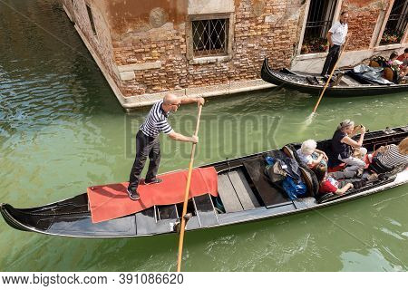 Venice, Italy - Sept 13, 2015: Two Gondoliers And Tourists On The Gondolas, Typical Venetian Rowing