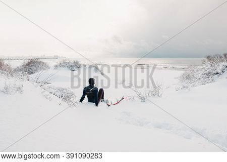 Cold Winter And Surfer Sit On Snowy Beach With Surfboard And See At Waves. Winter Day With Surfer In
