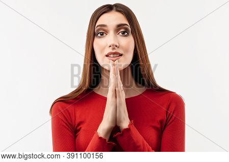 Portrait Of Joyous Brunette Woman With Long Hair In Casual Red Sweater Keeping Palms Together And Pr