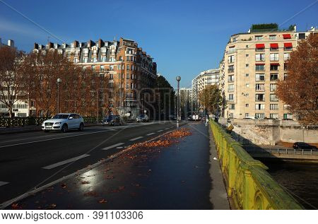 Paris, France - November 21, 2018: Residential buildings district view from Pont Mirabeau on Seine river under blue sky in fall season with fallen leaves on wet road after rain