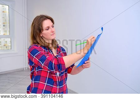 Woman Designer Draws A Plan Of The Future Room Standing In An Empty Apartment, One