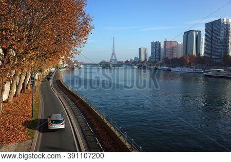 Paris, France - November 21, 2018: Paris cityscape with Eiffel tower, Pompidou Expressway along river Seine and modern building district on quai de Andre Citroen, Fall season sunny day blue sky