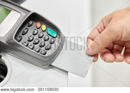 shopping, payment and finance concept - close up of hand with credit card in card-reader