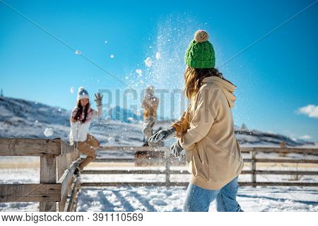 Happy Adult Girls Are Having Fun And Plays In Snowballs At First Snow In Mountains