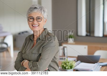 Portrait of a attractive mature woman with white hair and eyeglasses