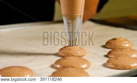 Chef Making Base For Preparation Macaron Dessert. Close-up Of Extruding Brawn Creme From Piping Bag