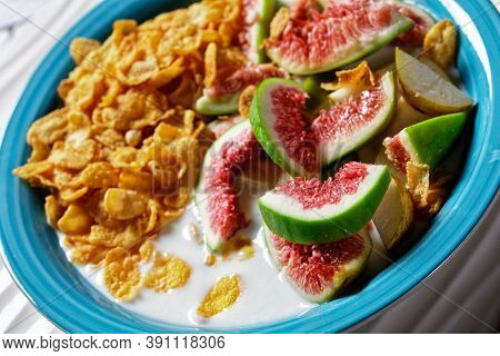 Blue Bowl With Natural Plain Yogurt With Crispy Cornflakes, Figs, Pear Served On A White Wooden Back