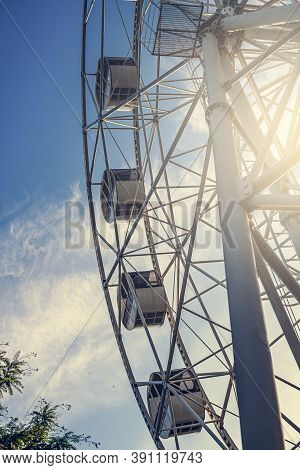 Gray Or White Metal Ferris Wheel With Closed Passenger Cabins Close-up In The Amusement Park