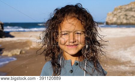 Portrait Of A Little Happy Child Girl Looking At Camera And Smiling At The Beach. Kid With Windswept