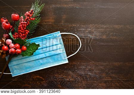 Medical Mask And Christmas Decor On A Brown Wooden Background. New Year / Christmas Layout, Top View