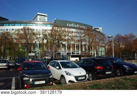 Paris, France - November 21, 2018: Cars on parking in front of Radio France headquarters circular building at Maison de la Radio, Fall season sunny day blue sky real unfiltered moment