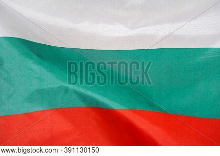 Fabric Texture Flag Of Bulgaria. Flag Of Bulgaria Waving In The Wind. Bulgaria Flag Is Depicted On A