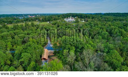 Aerial View Of Countryside With Star Barns And Cupolas And Covered Bridge On A Summer Day