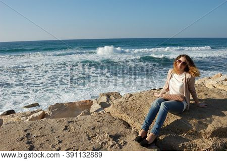 Young Curly Girl, Jeans, Glasses, Surf Rocks On Vacation By The Sea, Tourism, Blue Sea