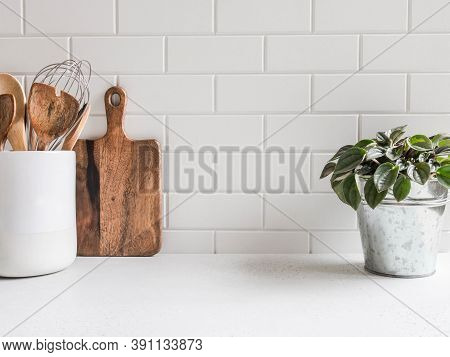 Stylish White Kitchen Background With Kitchen Utensils And Green Houseplant Standing On White Counte