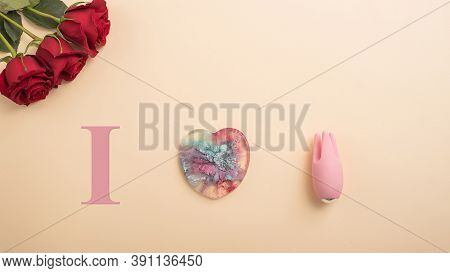 I Love To Masturbate. Rose Heart And Clitoral Vibrator On A Beige Background. Flat Lay