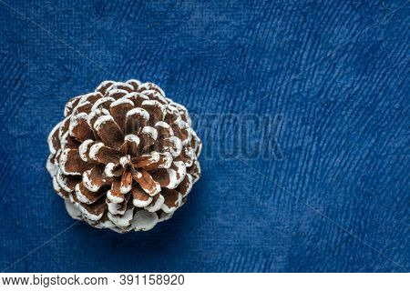 frosty decorative pine cone against blue handmade paper with a copy space, winter holidays background