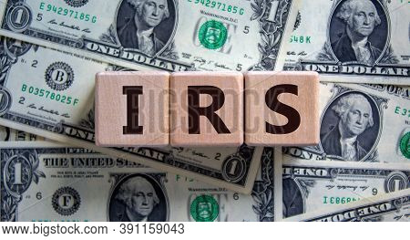 Concept Word 'irs - Internal Revenue Service' On Wooden Blocks On A Beautiful Background From Dollar