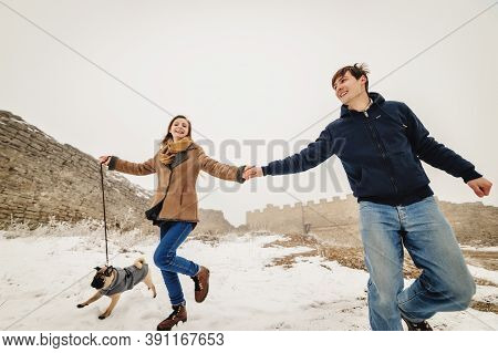 Lovely Couple In The Winter Field On A Walk With The Dog. Dog Walking With Owner Outdoor Snowy Natur