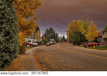 Fort Collins, CO, USA - October 22, 2020: A midday view of a residential street under heavy smoke plume from mountain forest wildfire - unhealthy levels of air pollution,