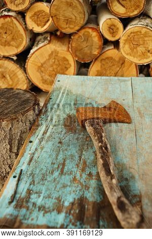 Old Rusty Ax Lies On The Blue Shabby Table Near Logs Of Birch Wo