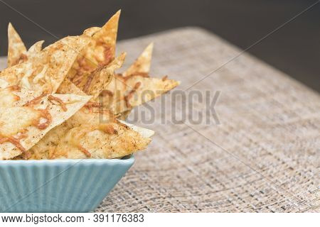 Homemade Nachos With Cheese, Olive Oil, Herbs And Spices In Turquoise Square Bowl On Rustic Fabric N