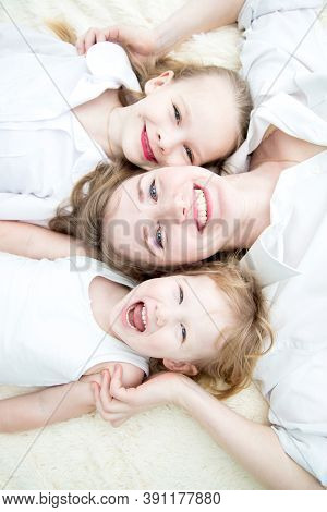 Portrait Of Mom And Her Daughters Smiling On The Bed Topview