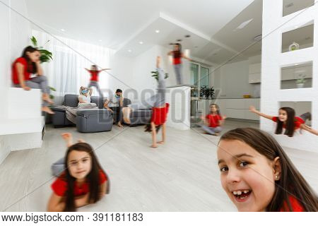 Annoyed Young Parents Sit On Couch In Kitchen Tired From Loud Little Daughter Running Playing, Anxio