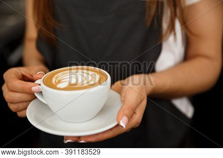 Coffee Business Concept - Cropped Close Up Of Female Serving Coffee With Latte Art While Standing In
