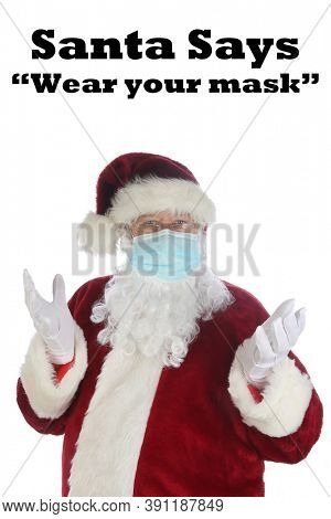 Santa says WEAR A MASK. Santa Claus wears a Medical Paper Face Mask to help prevent contracting the Coronavirus. Isolated on white. Room for text. Covid-19 is Dangerous. Its a COVID-19 Christmas.